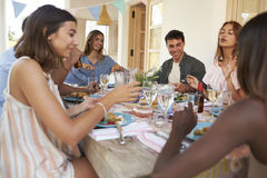 Friends sitting at a dinner party on a patio, close up Royalty Free Stock Photos