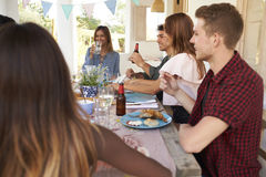 Friends sitting at a dinner party on a patio, close up Royalty Free Stock Photography