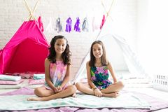 Friends Sitting On Duvets Against Tipi Tents During Pajama Party. Portrait of cute best friends sitting on duvets against tipi tents during pajama party at home royalty free stock photo