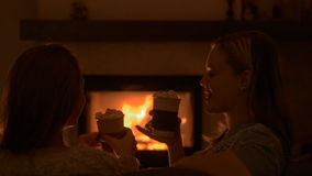 Friends sitting by the fire. Girls sitting at home by the fireplace and drinking cacoa with marshmallows stock footage