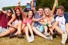 Friends sitting on the grass cheering at a music festival Stock Photo