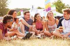Friends sitting on grass and eating at music festival Stock Images