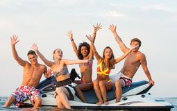 Friends sitting on a jet ski. Group of happy multi ethnic friends sitting on a jet ski Royalty Free Stock Photos