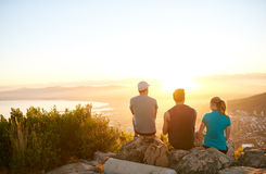 Friends sitting on a mountain trail watching the sunrise togethe Stock Images