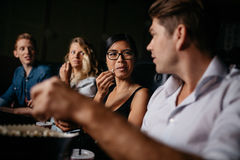 Friends sitting in multiplex movie theater. Group of friends sitting in multiplex movie theater and talking. Young people in cinema with popcorn Stock Photography