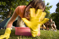 Friends sitting near tent in woodland clearing, focus on young woman in yellow washing up gloves kneeling beside pink bowl, waving Stock Images