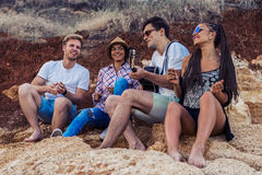 Friends Sitting On Stones On Beach. Man Is Playing Guitar. Stock Photos