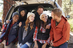 Friends sitting in the open back of a car look at each other Stock Photo