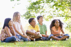 Friends sitting outdoors with soccer ball Royalty Free Stock Image