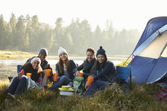 Friends sitting outside a tent near a lake looking to camera Royalty Free Stock Photography