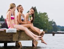 Friends sitting on pier Royalty Free Stock Photography