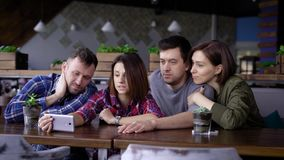 Friends sitting at the restaurant together and using digital smartphone. Two handsome men and two smiling women looking. Group of people are sitting at the stock footage
