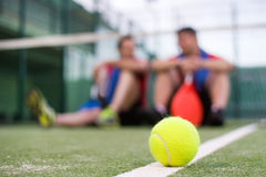 Friends sitting resting after a game of paddle tennis Royalty Free Stock Image