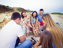 Friends sitting on the sand at the beach in circle with marshmal. Low on the beach Stock Photo