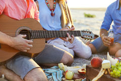 Friends sitting on the sand at the beach in circle. One man is p Royalty Free Stock Photo
