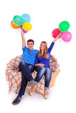 Friends sitting on a sofa with balloons Royalty Free Stock Images