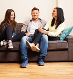 Friends sitting on a sofa Stock Images