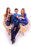 Friends sitting on a sofa and drinking Coca Cola Stock Photography