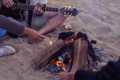 Friends sitting on stones on beach. man is playing guitar. Closeup view of young and cheerful friends sitting on beach. and lit bonfire One man is playing Stock Photography
