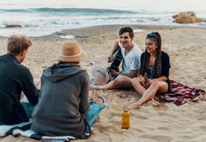 Friends sitting on stones on beach. man is playing guitar. Group of young and cheerful friends sitting on beach and lit bonfire. One men is playing guitar Royalty Free Stock Images