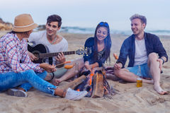 Friends sitting on stones on beach. man is playing guitar. Group of young and cheerful friends sitting on beach and lit bonfire. One men is playing guitar Stock Photography