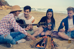 Friends sitting on stones on beach. man is playing guitar. Group of young and cheerful friends sitting on beach and lit bonfire. One men is playing guitar Royalty Free Stock Image