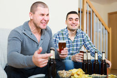 Friends sitting at table with beer Royalty Free Stock Images