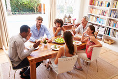 Friends sitting at a table talking during a dinner party Royalty Free Stock Photos