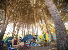 Friends sitting together at campsite. Friends sitting together by trees at campsite Royalty Free Stock Photo