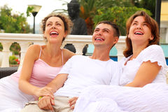 Friends sitting together on couch outdoors. Three friends sitting together on couch outdoors and laughing, focus on man Stock Image