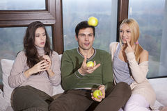 Friends sitting together on the sofa having fun Stock Images