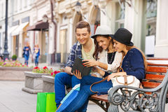 Friends sitting together with tablet on the bench. On the beautiful street during summer day time in Europe Stock Photo