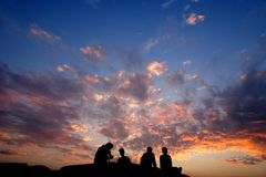 Friends sitting on top of a rock during sunset silhouette royalty free stock image