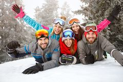 Friends on skiing laying together on snow. Happy young friends on skiing laying together on snow Stock Photos