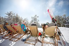 Friends on skiing sunbathing in sunbed on ski terrain, back view. Friends resting on skiing and sunbathing in sunbed on ski terrain, back view Royalty Free Stock Image