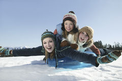 Friends Sledding At Winter Time Stock Photo