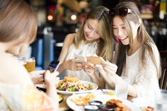 Friends with smart phones taking picture of food. Happy friends with smart phones taking picture of food at restaurant Stock Image