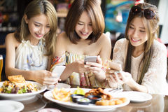 Friends with smart phones taking picture in restaurant Royalty Free Stock Photos