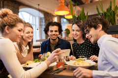 Friends with smartphone eating at restaurant. Leisure, food, drinks, people and holidays concept - happy friends with smartphone eating and drinking at stock images