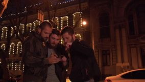 Friends with a smartphone are looking for a place in the night city. The group of tourists was lost. With the help of the map young men learn where to go stock video footage