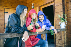 Friends with smartphone on a rainy day Royalty Free Stock Image