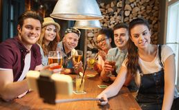 Friends with smartphone on selfie stick at bar Royalty Free Stock Images