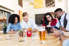 Friends with smartphone, tablet pc and beer at bar. Leisure, technology and people concept - group of happy international friends with smartphones and tablet pc Royalty Free Stock Image