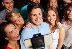 Friends with smartphone taking selfie in club Stock Images