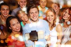 Friends with smartphone taking selfie in club. Party, technology, nightlife and people concept - smiling friends with smartphone and monopod taking selfie in Stock Image