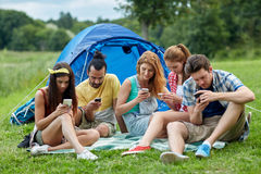Friends with smartphone and tent at camping. Travel, tourism, hike, technology and people concept - group of friends with smartphone and tent at camping stock photos