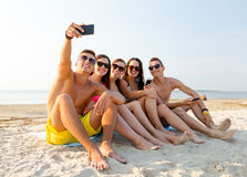 Friends with smartphones on beach. Friendship, leisure, summer, technology and people concept - friends sitting and taking selfie with smartphone on beach Stock Photography