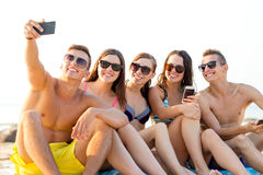 Friends with smartphones on beach Stock Image