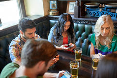 Friends with smartphones and beer at bar or pub. People, leisure, friendship and communication concept - friends with smartphones drinking beer and texting at Royalty Free Stock Images