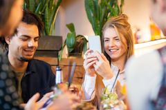 Friends with smartphones eating at restaurant Royalty Free Stock Photo